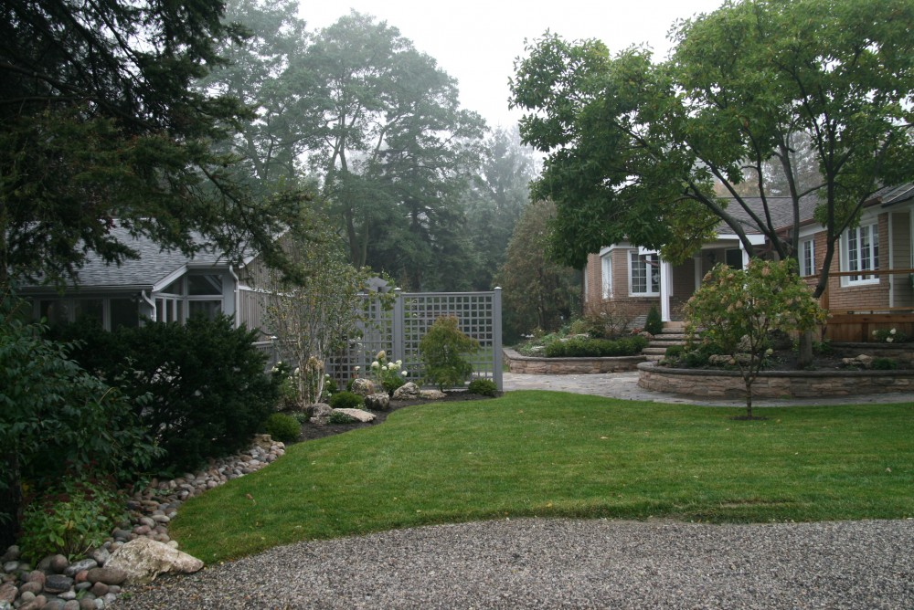 This was an extensive project to update the existing landscaping. Overgrown trees and shrubs were removed. The crumbling retaining walls were replaced. A fence, arbor and columnar beeches were added to block the view of the adjacent house. A courtyard patio was created with a privacy fence to screen the side yard from the road. A fountain, a teak bench and an oversize urn complete the seating area. New plantings were installed throughout.