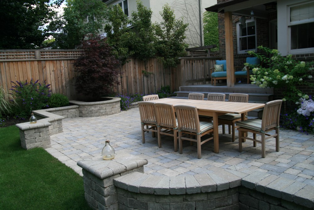 We transformed this back yard by removing an old unused garage and reclaiming part of the driveway. The client wanted a large patio to to hold a sizable table for family gatherings. Incorporating a seating wall into the patio design provides extra seating for entertaining. A small corner shed from Summerwood adds to the aesthetics. A new fence and columnar pears provide privacy.